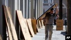 Preston Guiher carga un panel de madera prensada mientras se prepara cubrir un banco de Wells Fargo en anticipación a la llegada del huracán Florence, en Charleston, Carolina del Sur, el martes 11 de septiembre de 2018. (AP/Mic Smith)