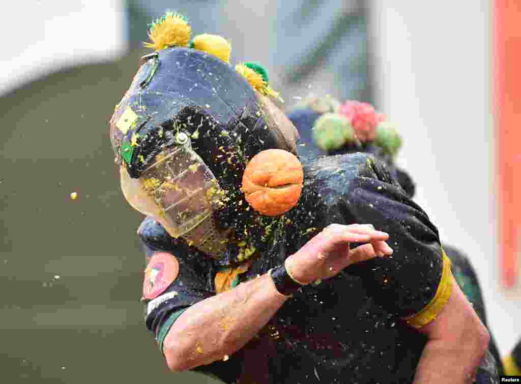 Revelers take part in a fight with oranges during an annual carnival battle in Ivrea, Italy.