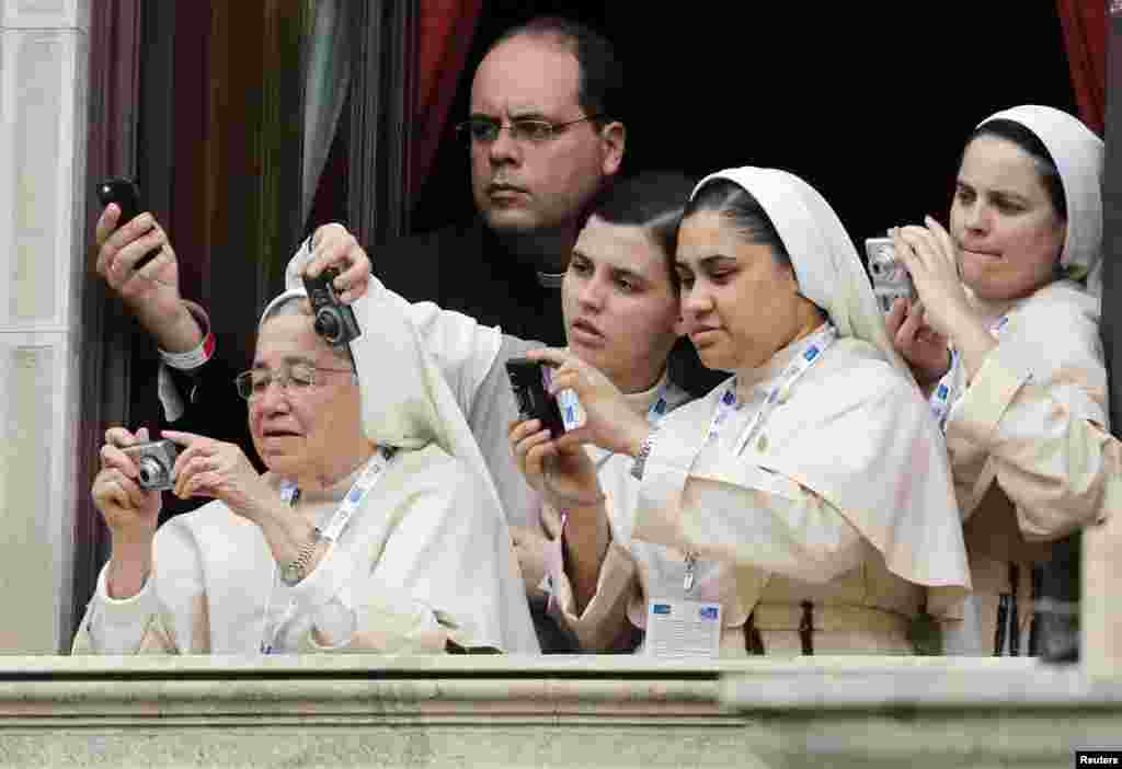 Nuns and a priest take pictures as Pope Francis arrives at Sao Joaquim Palace in Rio de Janeiro, July 26, 2013.