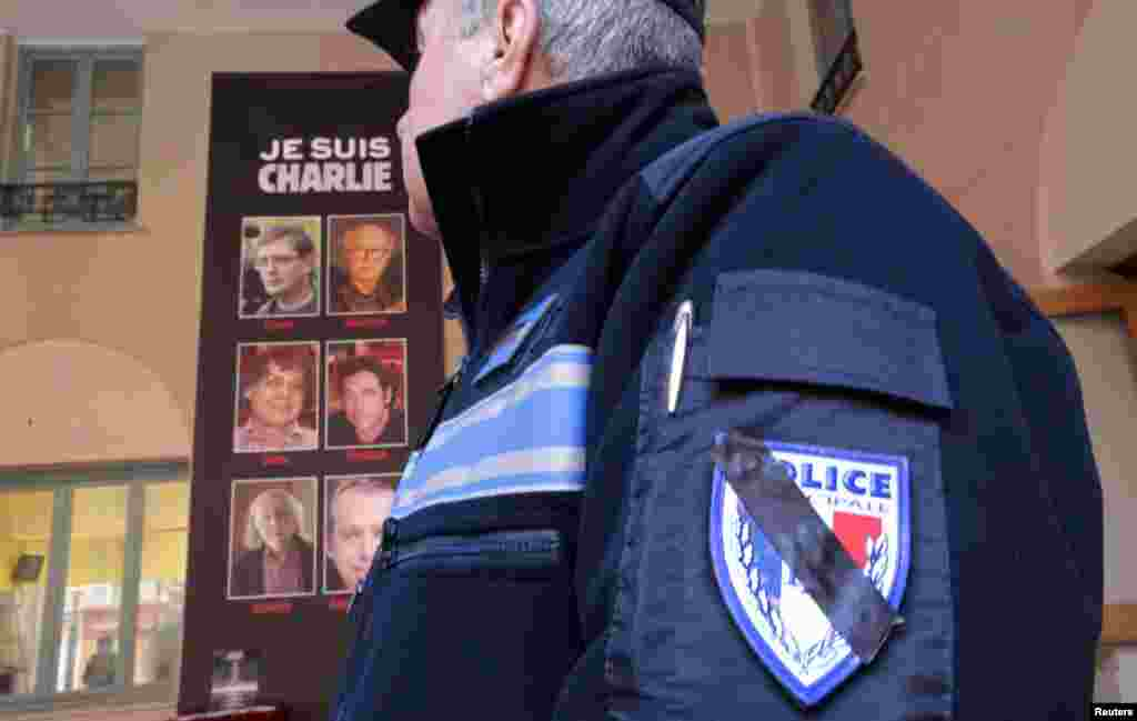 A French municipal police officer wears a black bar across his official police emblem as a symbol of mourning of the Charlie Hebdo shootings, in Nice, France, Jan. 8, 2015.