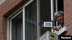Bà Trương Tiên Linh cầm ảnh của con trai bị binh sĩ Trung Quốc giết tại Quảng trường Thiên An Môn. Trong khi bà mẹ 77 tuổi này chuẩn bị ngày giỗ thứ 25 cho con, bà bị 8 nhân viên an ninh và cảnh sát canh chừng ngày đêm