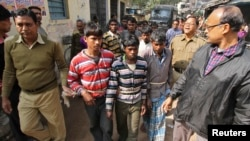 Indian police personnel escort men, tied with rope, who are accused of a gang-rape, to a court at Birbhum district in the eastern Indian state of West Bengal, Jan. 23, 2014.