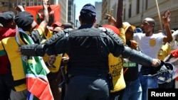 A police officer tries to control ANC supporters as they attempt to confront members of the opposition Democratic Alliance party marching in central Johannesburg, Feb. 12, 2014.