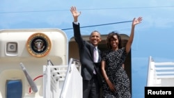 U.S. President Barack Obama and the First lady Michelle Obama wave from Air Force One upon their departure from Dar es Salaam, July 2, 2013.