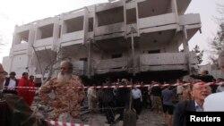 在被炸坏的法国驻利比亚大使馆外,人们站在废墟中围观