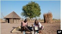 Feb. 8, 2010. Senwei Village, Terekeka Region, South Sudan. Guinea worm Eradication Program Village Volunteer Puru tends to her husband, Garbino's Guinea worm leg wound, at their home.