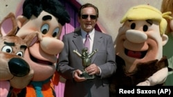 Joseph Barbera poses with famed Hanna-Barbera cartoon characters, from left, Scooby Doo, Fred Flintstone and Barney Rubble