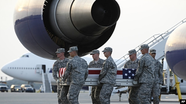 An Army carry team carries the transfer cases containing the remains of Army Spc. Scott D. Smith of Indianapolis, Indiana upon arrival at Dover Air Force Base, Delaware on June 21, 2011.