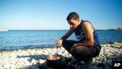 Un migrant cuisinant sur une plage de l'ile de Chios, en Grèce, le 29 septembre 2016.
