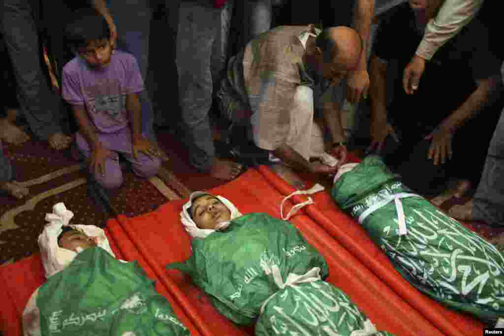 People gather around the bodies of three Palestinian teenage siblings from the Abu Musalam family, who medics said were shelled by an Israeli tank inside their house, during their funeral at a mosque in Beit Lahiya, in the northern Gaza Strip, July 18, 2014.