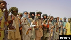 FILE - Baluch rebels holding their weapons.