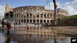 Niños juegan en un charco, junto al Coliseo en Roma, un día después de que fuertes cientos y aguaceros azotaran la capital italiana.