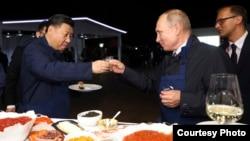 普京2018年9月11日與到訪的習近平碰杯。