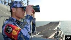 중국의 첫 항공모함 '랴오닝' 호가 지난달 26일 동중국해에서 훈련 중인 가운데, 한 승무원이 갑판에서 해상을 점검하고 있다. (자료사진)