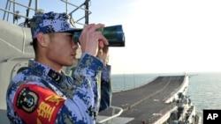 Anggota angkatan laut China melakukan pengawasan dari dek kapal Liaoning, dalam uji coba pelayaran di Laut China Timur. (Foto: Dok)