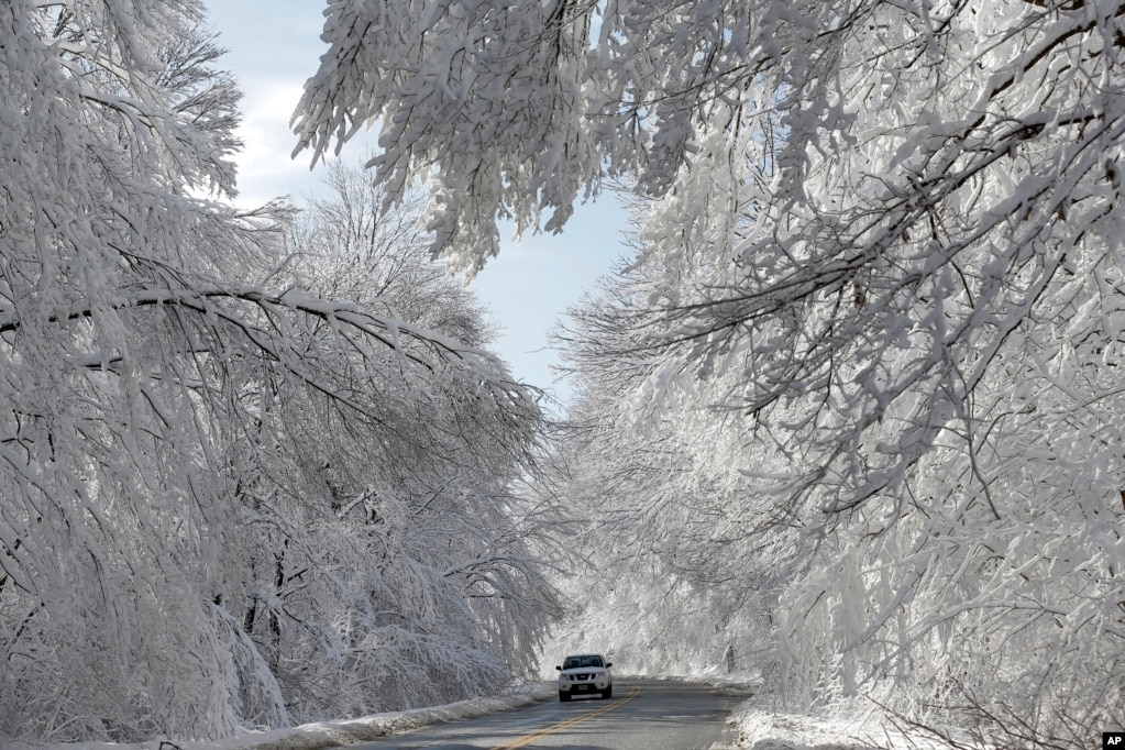 A car makes its way through a snowy area in Highland Falls, New Jersey.