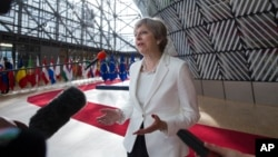 British Prime Minister Theresa May speaks with the media as she arrives for an EU summit at the Europa building in Brussels, June 23, 2017. European Union leaders meet in Brussels on the final day of their two-day summit to focus on ways to stop migrants crossing the Mediterranean and how to uphold free trade while preventing dumping on Europe's markets.