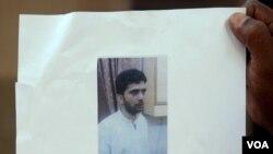 一位男士在孟買的一次新聞發佈會上舉著印度警方發佈的恐怖主義策劃人亞辛‧巴克 托的圖片。