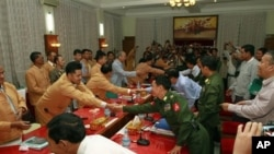 Members of Myanmar government negotiators, right, shake hands with representatives of the Shan State Army (SSA).