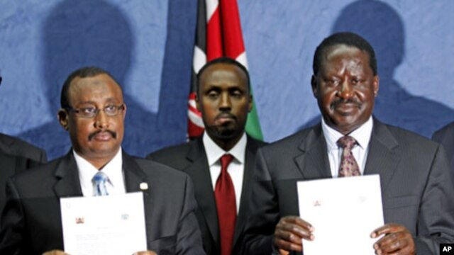 Somalia's Prime Minister Abdiweli Mohamed Ali (L) and his Kenyan counterpart Raila Amollo Odinga display the joint communique issued following their talks in Kenya's capital Nairobi, October 31, 2011.