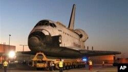 Phi thuyền con thoi Atlantis dài 16 kilomet từ nhà chứa phi cơ tới khu khách đến thăm trong Trung tâm Không gian Kennedy ở Florida.