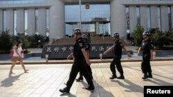 Polisi berpatroli di depang pengadilan tempat persidangan terpidana serangan maut dengan pisau di Kunming, Yunan. (Foto: Dok)