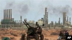 Wapiganaji wa waasi wakijitayarisha kwa mashambulio mbele ya kampuni ya kusafisha mafuta katika mji wa mashariki wa Ras Lanouf , Libya.