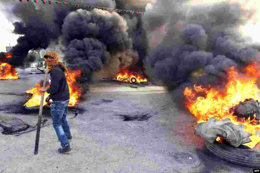 "A protester walks in front of burning tires as they block a street in Libya's second city of Benghazi after the killings of two policemen. The fatal shootings of the two officers came just a day after the U.N. mission in Libya voiced ""deep concern"" over the near-daily violence plaguing the North African country, particularly the east."