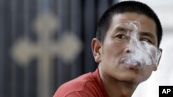 FILE - A man smokes a cigarette outside a church in Beijing.