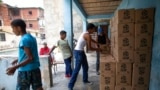Residentes ayudan a descargar y apilar cajas de alimentos básicos, como pasta, azúcar y harina, proporcionados por un programa de asistencia alimentaria del gobierno, en el barrio pobre de Petare, en Caracas, el 30 de abril de 2021