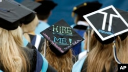 FILE - Graduates, including one looking for a job, are seated during George Washington University's commencement exercises on the National Mall in Washington, May 17, 2015.