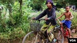 Im Chaem, a former Khmer Rouge cadre, is riding a bike along with her grandson in Anlong Veng, in Oddar Meanchey province in Cambodia, Sunday April 23, 2017. (Sun Narin/VOA Khmer)