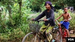 FILE PHOTO - Im Chaem, a former Khmer Rouge cadre, is pictured riding a bike along with her grandson in Along Veng, Oddar Meanchey province, Cambodia, Sunday, April 23, 2017. (Sun Narin/VOA Khmer)