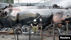 A police officer looks at the train wreckage in Lac-Megantic, July 9, 2013.