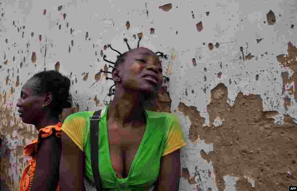 Two women mourn the death of two relatives killed in the 5th district, one the of the city's central neighborhoods, in Bangui, Central African Republic. The International Criminal Court in the Hague said on February 7 it had opened an initial probe into war crimes in CAR.