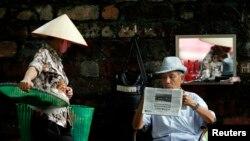 """Một người dân đọc báo trên đường phố Hà Nội. Theo thống kê của CPJ, Việt Nam kết án tù 11 nhà báo trong năm qua và trở thành một trong những quốc gia """"cai ngục"""" tồi tệ nhất thế giới."""
