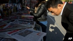 "A man looks over near the front page of a Chinese newspaper showing a photo of the typhoon damage in the Philippines and the white characters on blue which reads ""U.S. and Europe hype up Chinese aid to Philippines as 'Not Generous'"", at a newsstand in Beijing, Nov. 14, 2013."