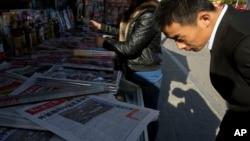 Seorang pria membaca koran China yang dijual di kios di Beijing.