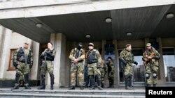 Para anggota pasukan bersenjata pro-Russia berjaga di depan kantor pemerintah di Slovyansk, wilayah Donetsk, Ukraina Timur (14/4).