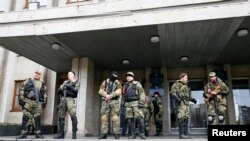 Pro-Russia armed men stand guard outside the mayor's office in Slovyansk, Donetsk region, eastern Ukraine, April 14, 2014.