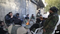 FILE - Rebel fighters of al-Jabha al-Shamiya (Levant Front) warm themselves around a fire near the justice palace in the old city of Aleppo, Syria, Jan. 28, 2016.