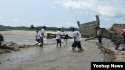 지난 7월 내린 비로 북한이 수해를 당한 가운데 북한의 한 지역에서 무너진 교각을 조선적십자 관계자들이 복구하고 있다.