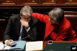 Italian Prime Minister Paolo Gentiloni talks with his Minister of Relations Anna Finocchiaro after giving his first speech as prime minister, Tuesday, Dec. 13, 2016.