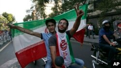Iranians attend a street celebration in Tehran, after their national soccer team qualified for the 2014 World Cup by defeating South Korea, June 18, 2013.