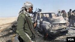 Los rebeldes libios observan los restos de uno de los vehículos destruidos de las fuerzas de Gadhafi.