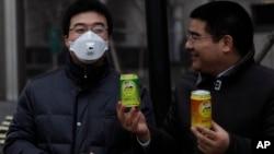 Multimiliuner Tiongkok, Chen Guangbiao (kanan) memberikan udara bersih kalengan pada seorang pria yang memakai masker udara karena polusi yang parah di Beijing (30/1). (Reuters/Barry Huang)