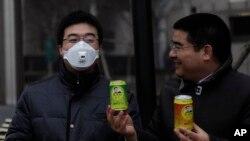 Doanh nhân triệu phú Trần Quang Tiêu (phải) đưa một lon không khí sạch cho một người đeo mặt nạ tại trung tâm thủ đô Bắc Kinh.