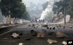 Rocks are scattered on a road, placed there by protesters, in Tegucigalpa, Honduras, Friday, Dec. 15, 2017.