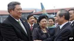 Indonesia's President Susilo Bambang Yudhoyono, left, shakes hands with Vietnamese minister Nguyen Van Chien, right, head of President's Office, as his wife Kristiani, center, stands by before their departure at the Noi Bai airport in Hanoi, 27 Oct 2010