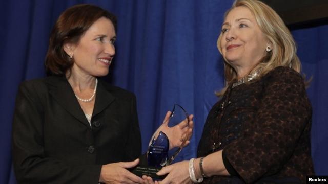 "Menlu AS Hillary Clinton (kanan) menyerahkan Penghargaan ""Common Ground"" untuk menghormati almarhum Christopher Stevens yang terbunuh di Libya kepada saudara perempuannya, Anne Stevens di Washington DC (8/11)."
